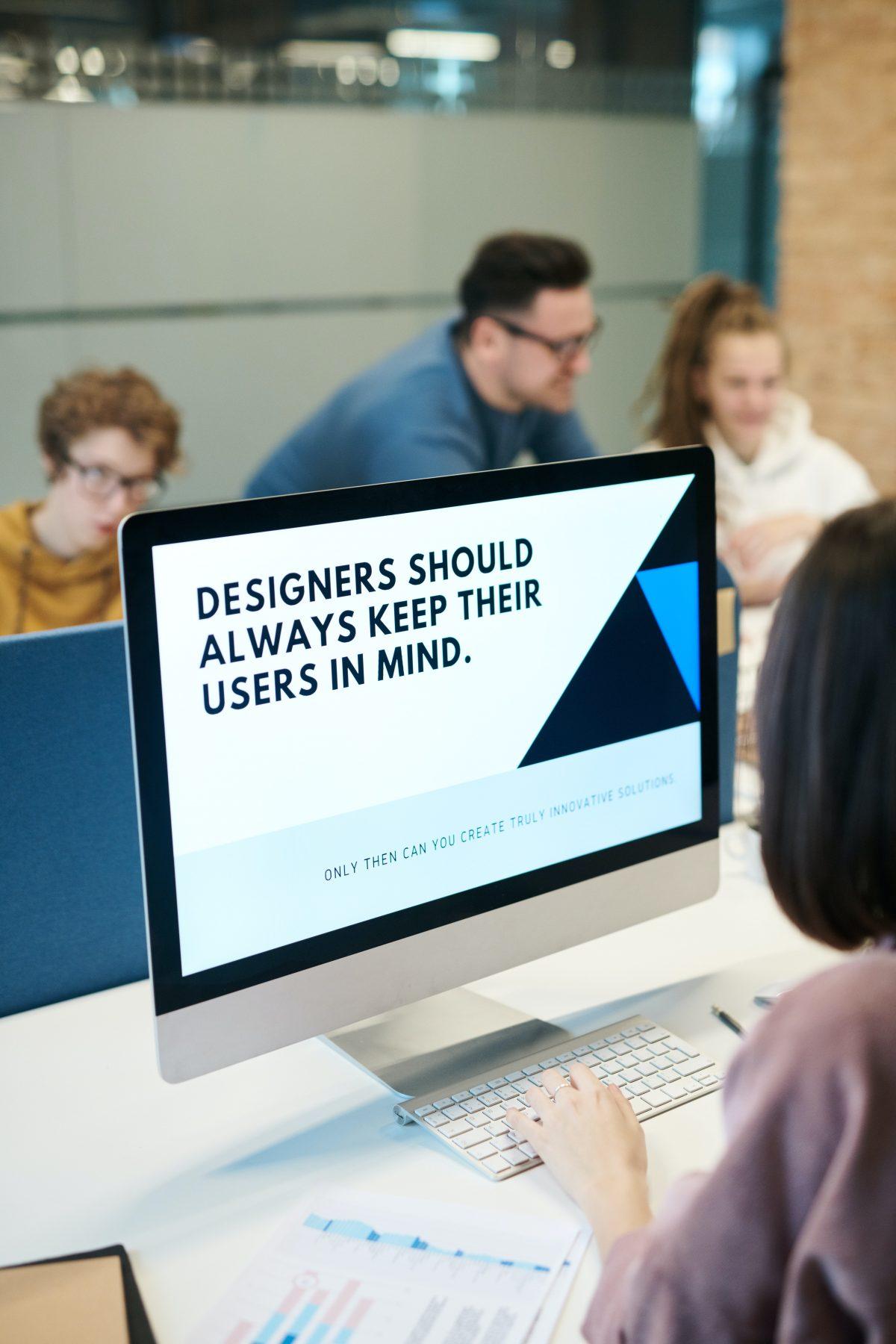 Mensen om een beeldscherm met 'Designers should always keep their users in mind' - credits: Fauxels via Pexels.com
