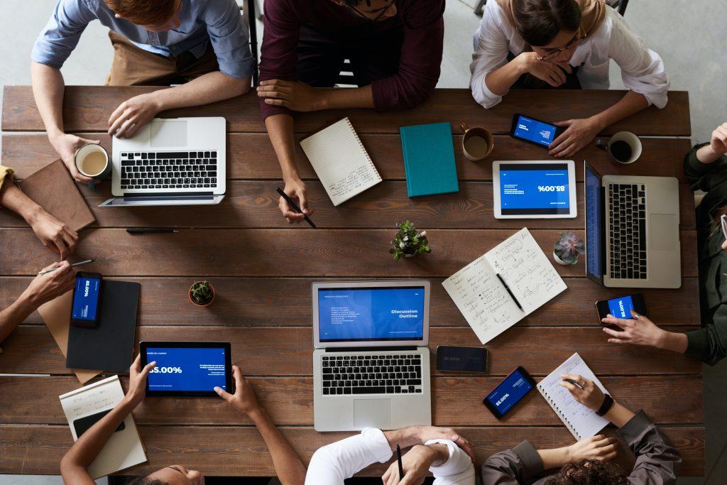 mensen aan tafel met verschillende devices